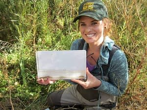 Kathleen Hemeon, University of Southern Mississippi, holding an unarmored threespine stickleback (Gasterosteus aculeatus williamsoni)